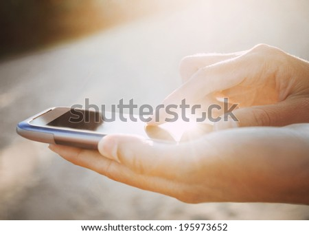 Woman hands holding a smart phone outdoor - stock photo