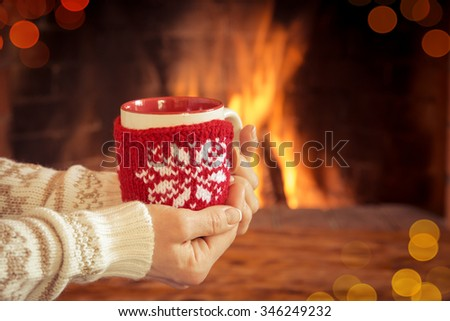 Woman hands holding Christmas cup near fireplace. Winter holiday concept - stock photo