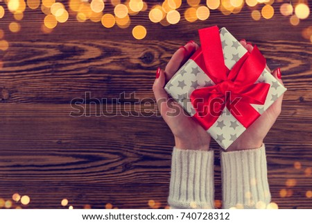 Woman hands holding Christmas gift, copyspace for text. Celebration and holidays concept. Colored in retro filter design. High resolution image
