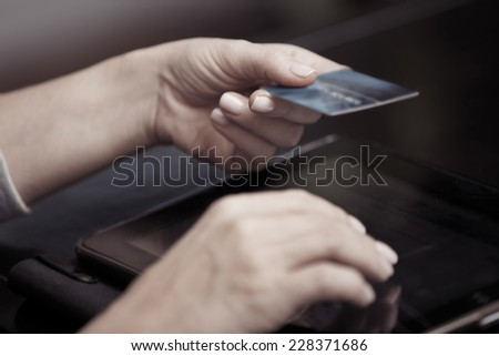 Woman hands holding credit card and tablet computer - stock photo
