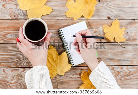 Woman hands holding cup of coffee on autumn wooden background. Autumn concept with yellow leafs, top view.