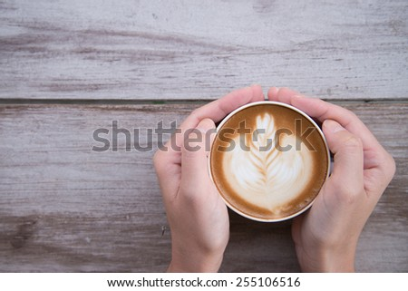 woman hands holding Latte art, coffee cup. - stock photo
