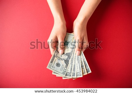 Woman hands holding money on red background - stock photo