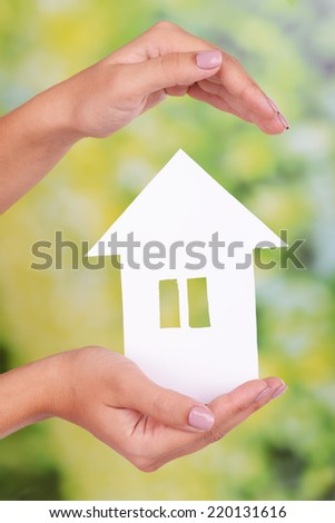 Woman hands holding paper house on bright background