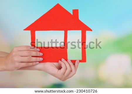 Woman hands holding paper house on bright background - stock photo