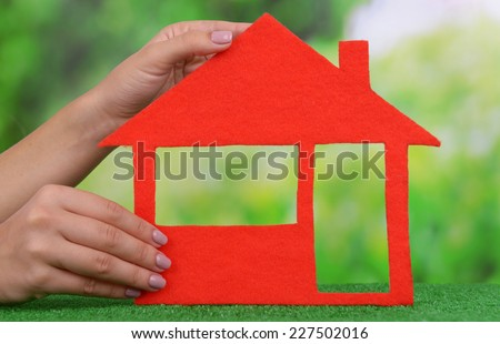 Woman hands holding paper house on grass on bright background