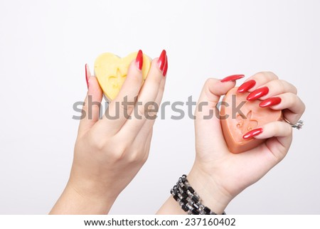 Woman hands holding soap with heart shape - stock photo
