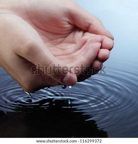 woman hands in blue water - stock photo