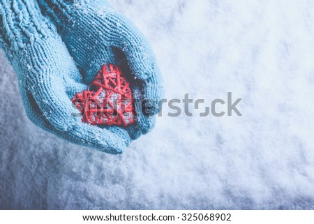 Woman hands in light teal knitted mittens are holding a beautiful a entwined vintage romantic red heart in a snow background. Love and St. Valentine concept. - stock photo