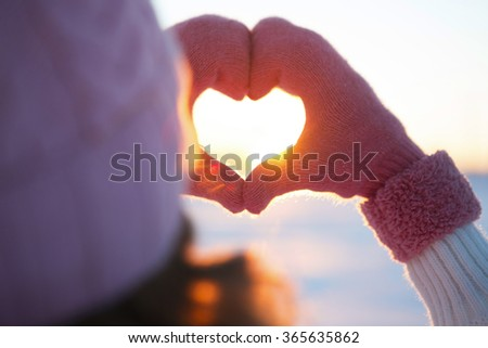 Woman hands in winter gloves Heart symbol shaped Lifestyle and Feelings concept with sunset light nature on winter background - stock photo