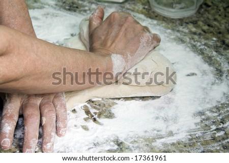 Woman hands kneading. Focus on dough. - stock photo