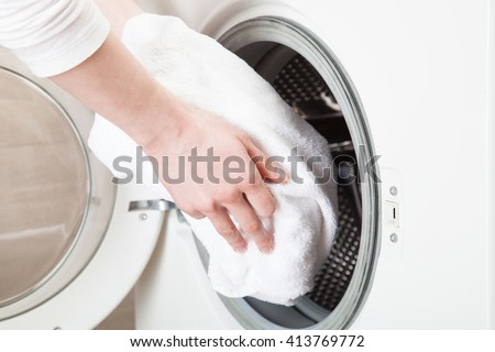 Woman hands loading linen into wahing machine - closeup shot - stock photo