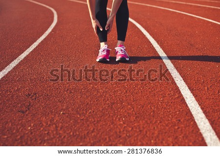 Woman hands massage her leg calf preparing for run front view. Sporty girl feet on a race track on stadium. Brightly lit scene. Copy space