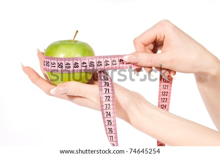 Woman hands measuring green apple over white - stock photo