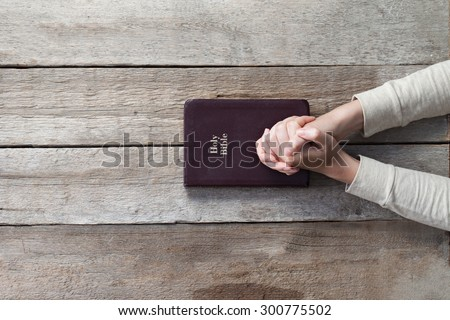 woman hands on bible. she is reading and praying over bible over wooden table - stock photo