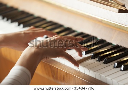 woman hands playing piano, selective focus - stock photo