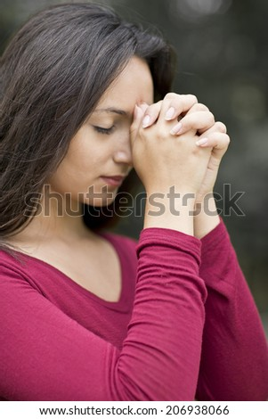 Woman hands praying with a blible in his legs Outdoors - stock photo
