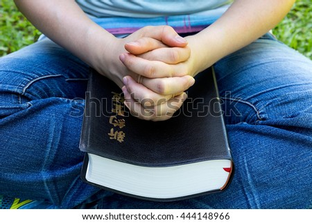 Woman hands praying with a Chinese New Testament holy bible in his legs Outdoors - stock photo