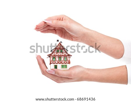 woman hands protect little house - stock photo