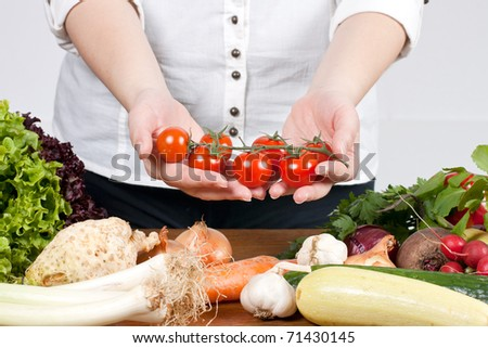 Woman hands showing fresh cherry tomato  with mixed vegetable.