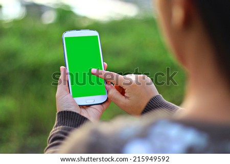 woman hands touching smartphone.green screen display - stock photo