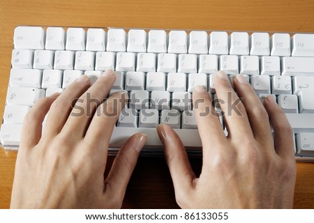 woman hands typing on a wireless white keyboard computer posed on a table - stock photo