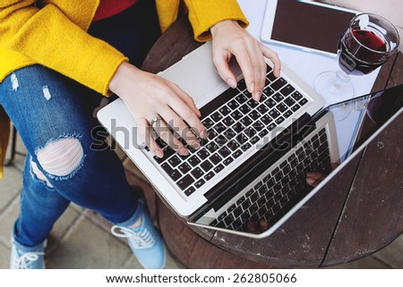 Woman hands typing on laptop, tablet and red wine outdoors in cafe - stock photo