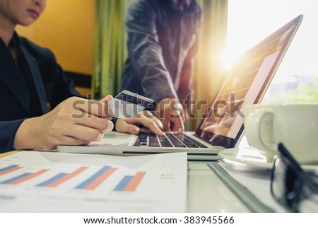 woman hands using laptop and holding credit card with digital business layers diagram as Online shopping concept in morning light. vintage effect - stock photo