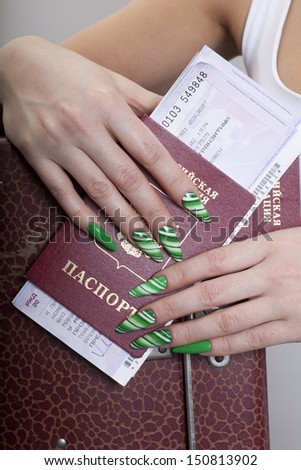 Woman hands with beautiful manicure with green nails and passport, tickets and bag around