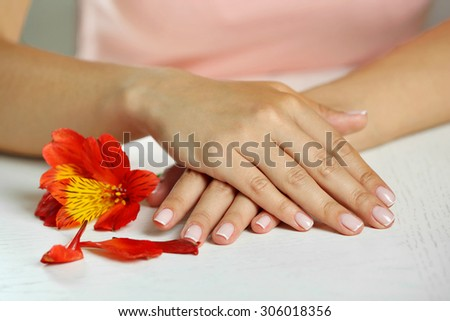 Woman hands with french manicure and flower on table close-up - stock photo