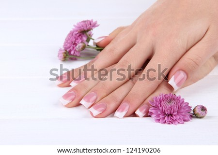 Woman hands with french manicure and flowers on white wooden background