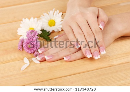 Woman hands with french manicure and flowers on wooden background