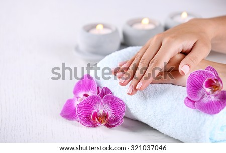 Woman hands with french manicure and orchid flowers on wooden table close-up - stock photo