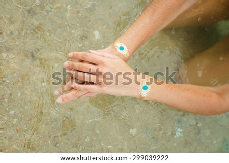Woman hands with gold sticker tattoo in the sea