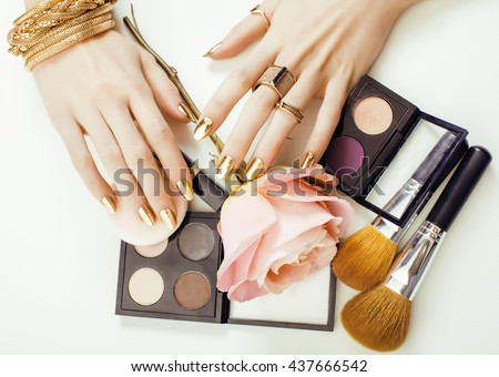 woman hands with golden manicure and many rings holding brushes, makeup artist stuff stylish, pure close up pink - stock photo