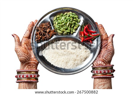 Woman hands with henna holding plate with rice and spices isolated on white background with clipping path  - stock photo