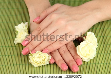 Woman hands with pink manicure and flowers, on bamboo mat background
