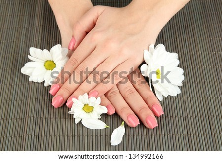 Woman hands with pink manicure and flowers, on bamboo mat background - stock photo