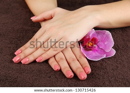 Woman hands with pink manicure and orchid on  dark color background - stock photo