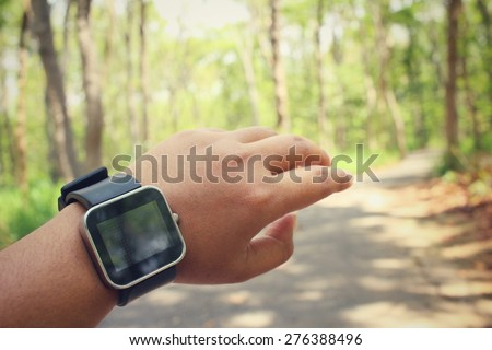 Woman hands with smartwatch in forest - stock photo
