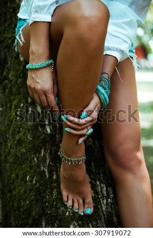woman hands with turquoise nail polish, ring and bracelets lean on legs, outdoor shot, selective focus - stock photo