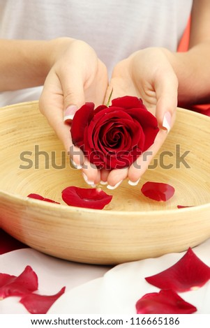 woman hands with wooden bowl of water with petals, on red background