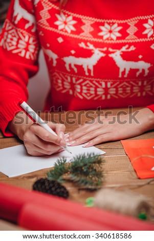 woman hands writing on christmas postcard, closeup hands - stock photo