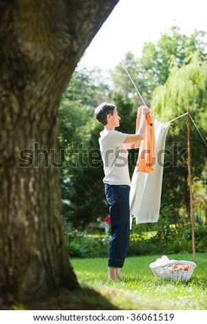Woman hanging clothes in her yard - stock photo