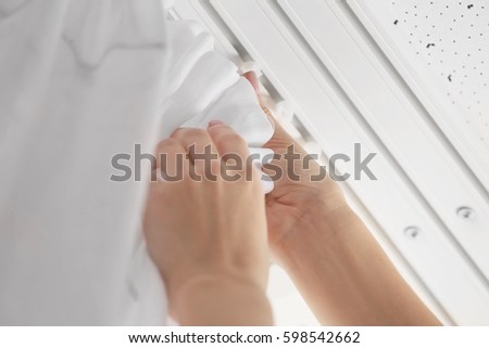 Woman hanging curtains over window, closeup