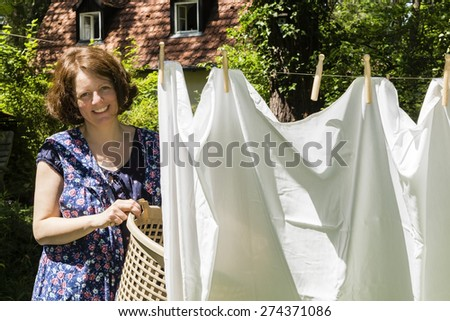 Woman Hanging up the washing in a garden - stock photo