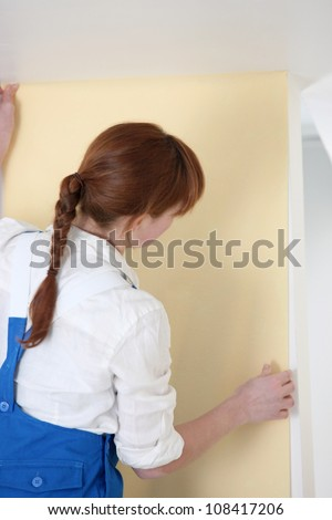 Woman hanging wallpaper - stock photo