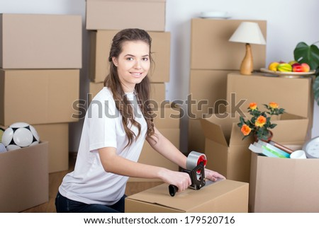 Woman happily unpacking moving boxes in living room - stock photo