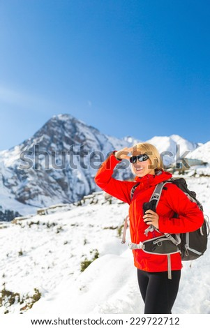 Woman happy smiling hiker nordic walking in Himalaya Mountains in Nepal. Trekking on snow white winter nature, beautiful mountain landscape. Achievement explore outdoors natural beauty view - stock photo