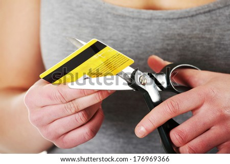 Woman has to destroy her credit card. Close up - stock photo